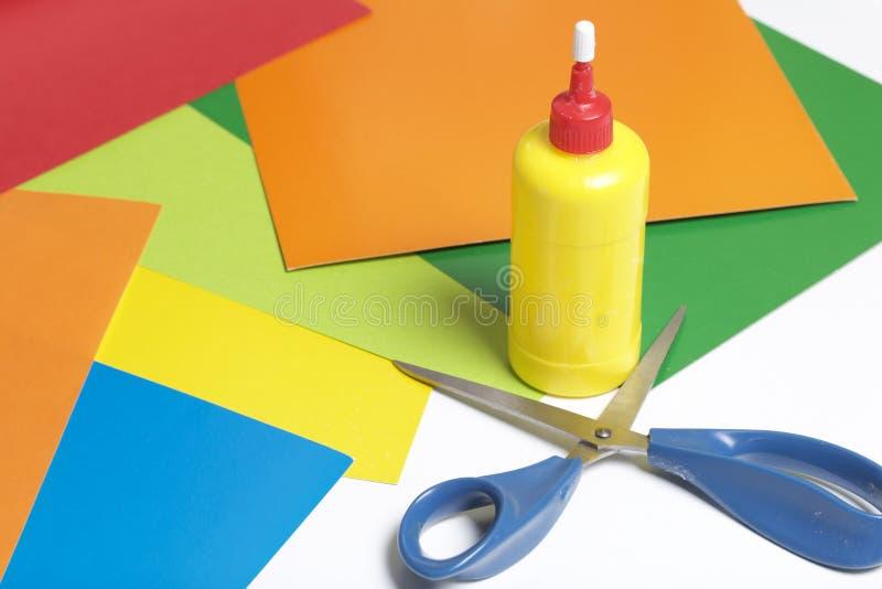 Lições no applique Artigos necessários: a colagem, o papel colorido e as tesouras encontram-se na superfície branca da tabela fotos de stock