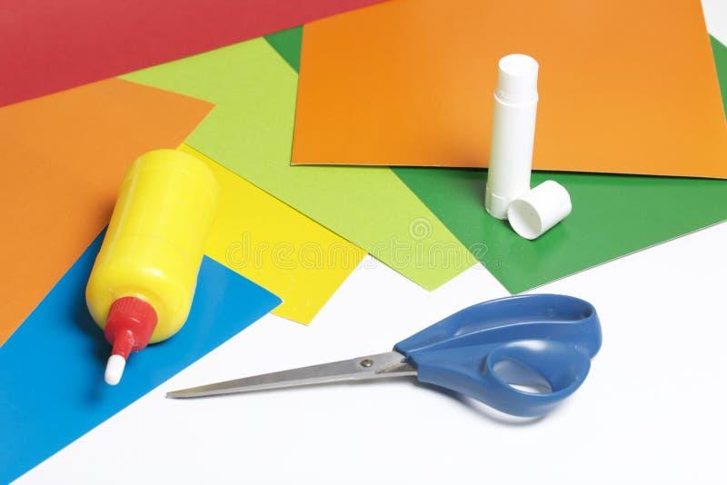 Lições no applique Artigos necessários: a colagem, o papel colorido e as tesouras encontram-se na superfície branca da tabela imagem de stock royalty free