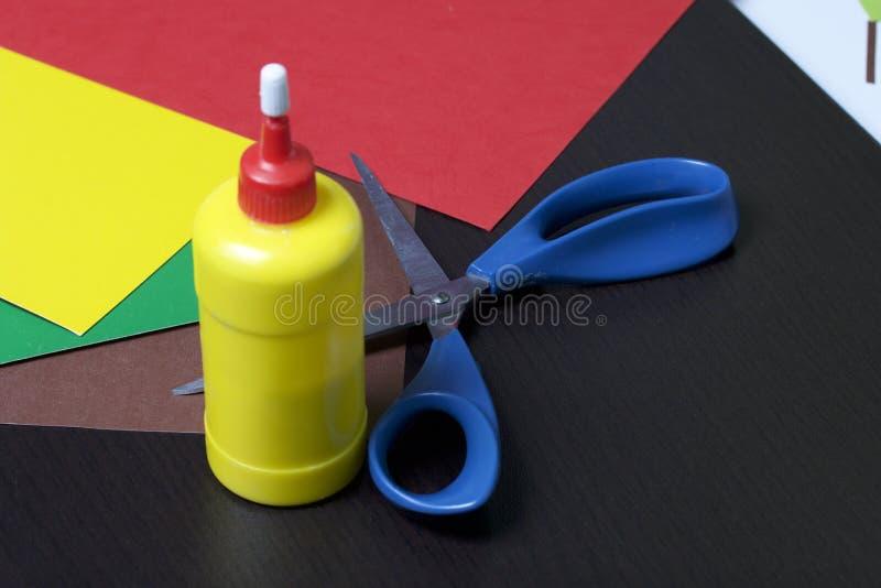 Lições no applique Artigos necessários: a colagem, o papel colorido e as tesouras encontram-se na superfície escura da tabela fotografia de stock