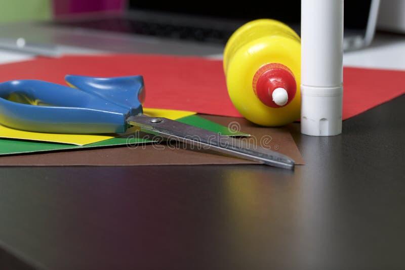 Lições no applique Artigos necessários: a colagem, o papel colorido e as tesouras encontram-se na superfície escura da tabela imagem de stock