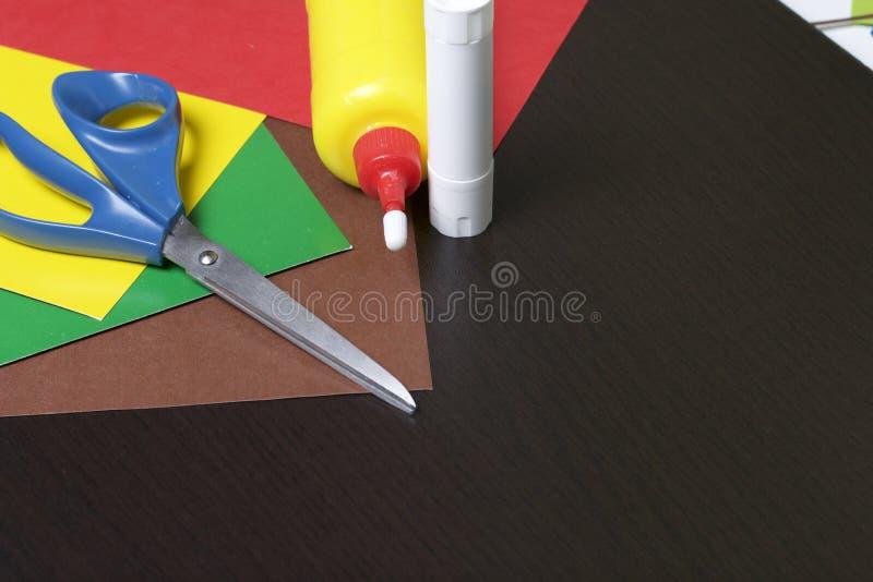 Lições no applique Artigos necessários: a colagem, o papel colorido e as tesouras encontram-se na superfície escura da tabela foto de stock royalty free