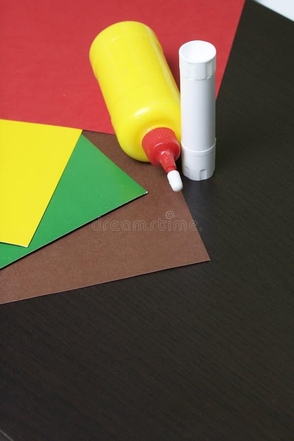 Lições no applique Artigos necessários: a colagem, o papel colorido e as tesouras encontram-se na superfície escura da tabela foto de stock