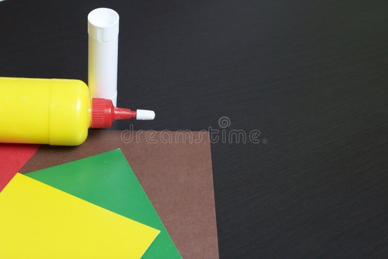 Lições no applique Artigos necessários: a colagem, o papel colorido e as tesouras encontram-se na superfície escura da tabela fotos de stock