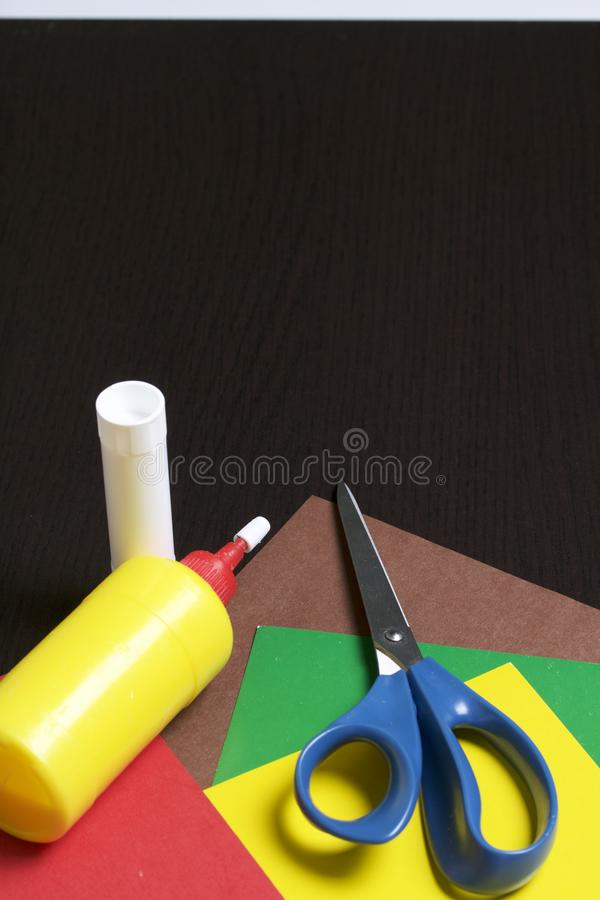 Lições no applique Artigos necessários: a colagem, o papel colorido e as tesouras encontram-se na superfície escura da tabela imagem de stock royalty free