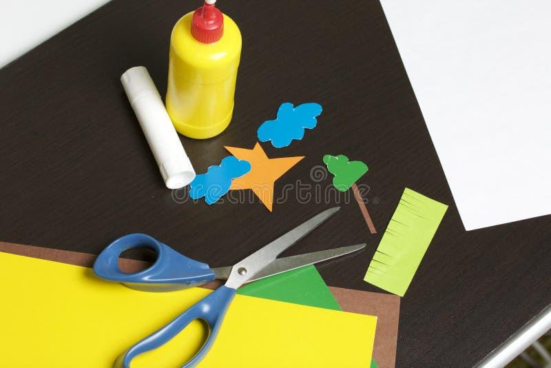 Lições no applique Artigos necessários: a colagem, o papel colorido e as tesouras encontram-se na superfície escura da tabela Cor fotografia de stock
