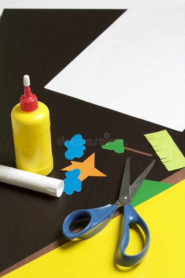 Lições no applique Artigos necessários: a colagem, o papel colorido e as tesouras encontram-se na superfície escura da tabela Cor fotos de stock