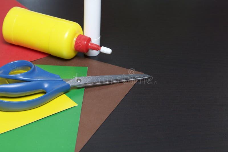 Lições no applique Artigos necessários: a colagem, o papel colorido e as tesouras encontram-se na superfície escura da tabela imagens de stock