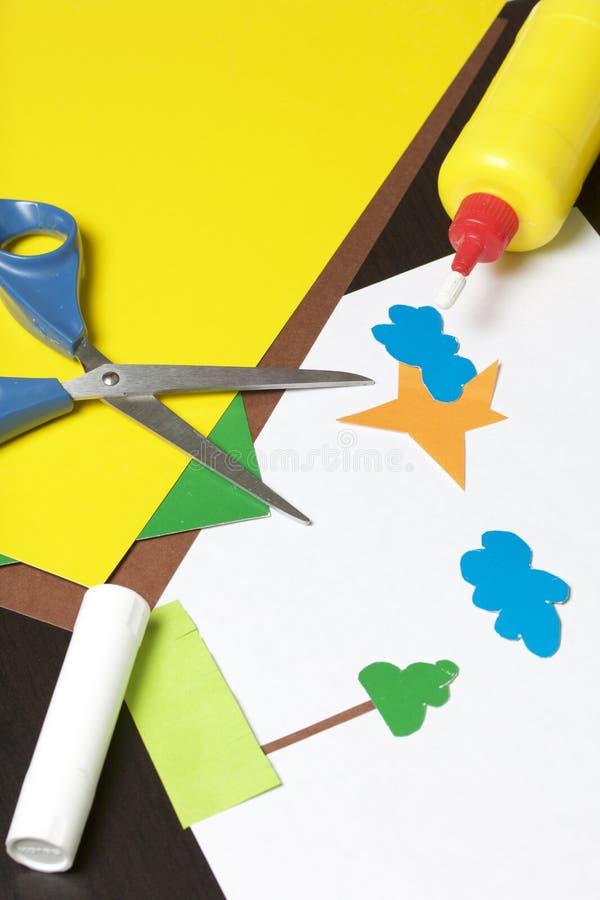 Lições no applique Artigos necessários: a colagem, o papel colorido e as tesouras encontram-se na superfície escura da tabela Cor imagem de stock royalty free