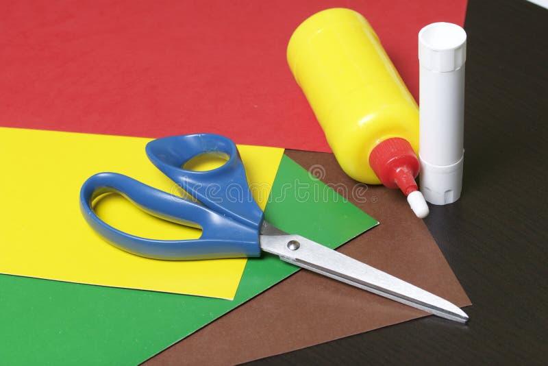 Lições no applique Artigos necessários: a colagem, o papel colorido e as tesouras encontram-se na superfície escura da tabela fotografia de stock royalty free