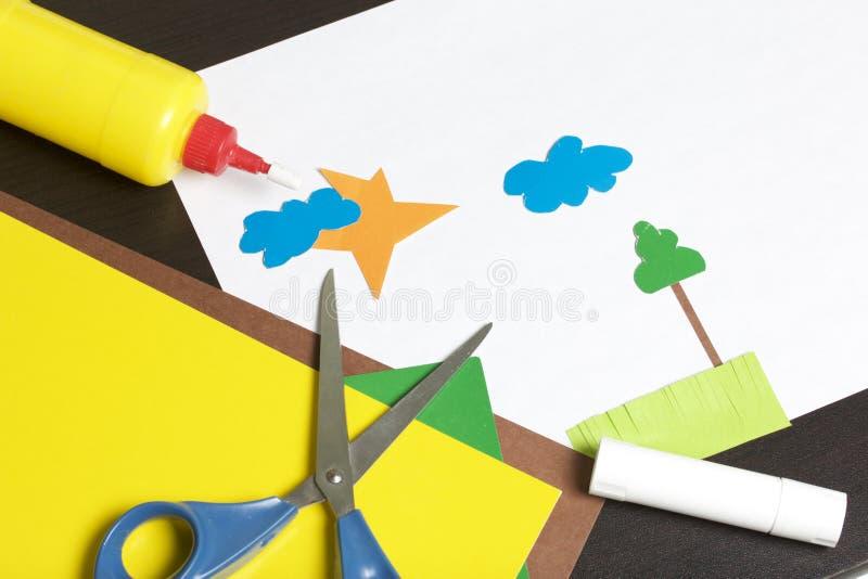 Lições no applique Artigos necessários: a colagem, o papel colorido e as tesouras encontram-se na superfície escura da tabela Cor foto de stock