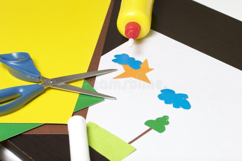 Lições no applique Artigos necessários: a colagem, o papel colorido e as tesouras encontram-se na superfície escura da tabela Cor foto de stock royalty free