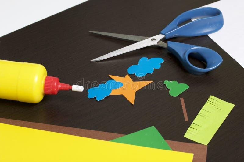 Lições no applique Artigos necessários: a colagem, o papel colorido e as tesouras encontram-se na superfície escura da tabela Cor imagens de stock royalty free