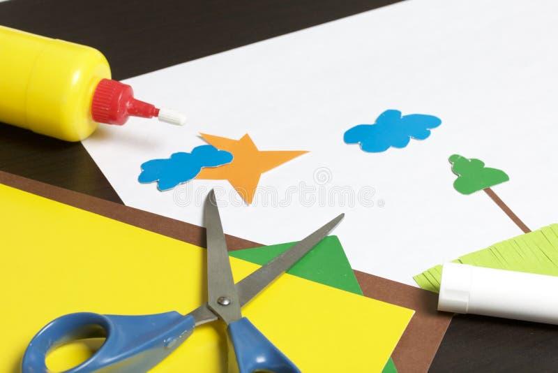 Lições no applique Artigos necessários: a colagem, o papel colorido e as tesouras encontram-se na superfície escura da tabela Cor imagens de stock