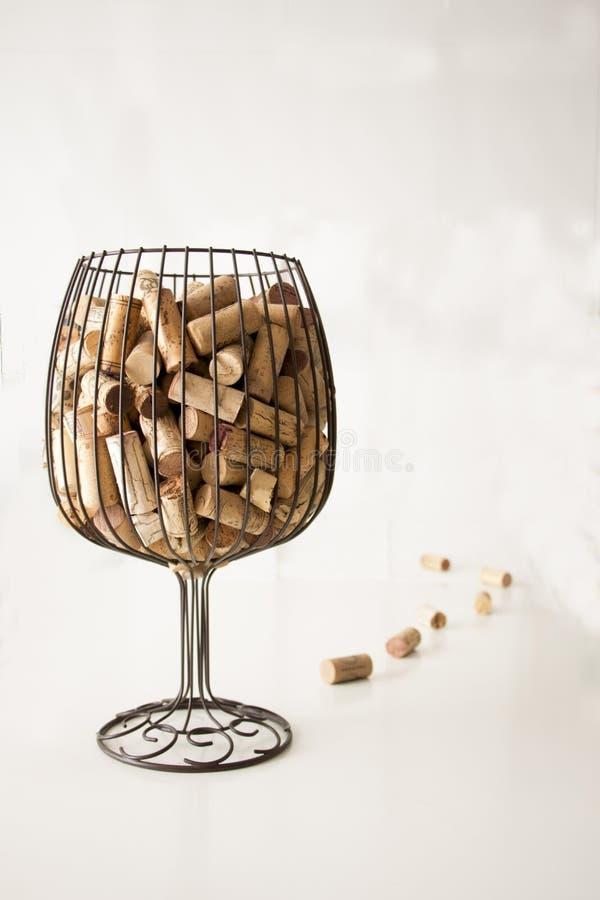 Lièges des bouteilles à l'intérieur d'un vase simulant un verre de vin et de quelques bouchons de liège à côté du vase avec un fo photographie stock libre de droits