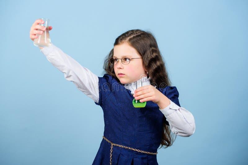 Li??o do bilogy do estudo da crian?a Descubra o futuro Cientista pequeno da menina com garrafa de teste Instru??o e conhecimento  fotografia de stock royalty free