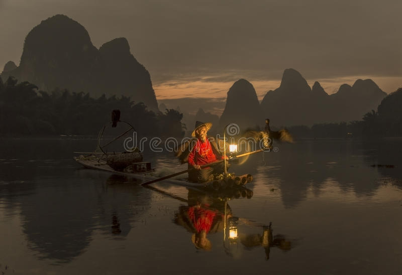 Li River - Xingping, China En enero de 2016 - una vieja pesca del pescador con sus cormoranes imágenes de archivo libres de regalías