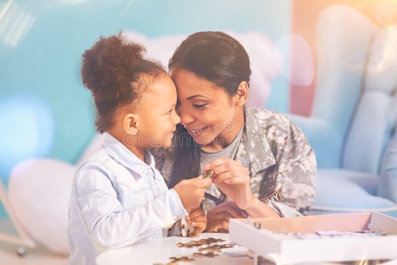 Liaison de mère et de fille tout en faisant un puzzle photographie stock