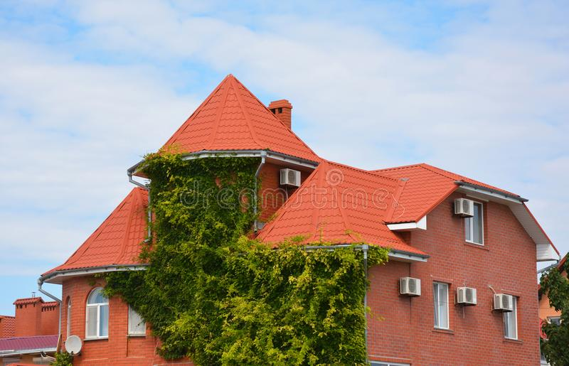 Liana on house wall. Modern brick house with metal roof and green lianas for better cooling home. royalty free stock photos