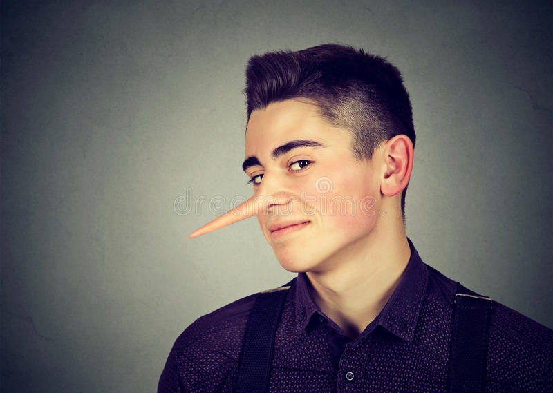 Liar funny looking young sly man. Liar funny looking young man royalty free stock photo