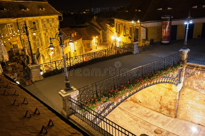 Liars Bridge Podul Minciunilor in Sibiu - view from above at night, with red flowers and street lamps glowing. stock image