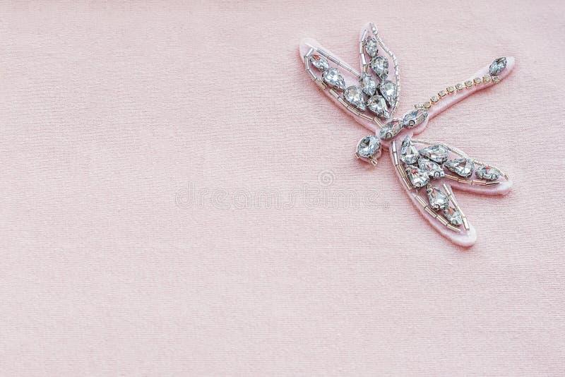 Libelbroche van bergkristallen en parels op roze stoffenachtergrond met exemplaarruimte Geborduurd bijkomend decor op kleren bove stock fotografie