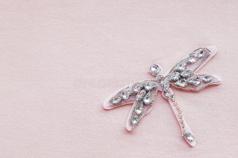 Libelbroche van bergkristallen en parels op roze stoffenachtergrond met exemplaarruimte Geborduurd bijkomend decor op kleren bove stock foto