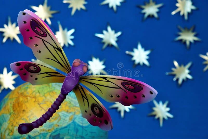 Libelle ist ein Symbol von Feen, Leichtigkeit, Anmut, Frivolität, Geschwindigkeit, auf dem Hintergrund der Kugel der Erde und des stockbilder