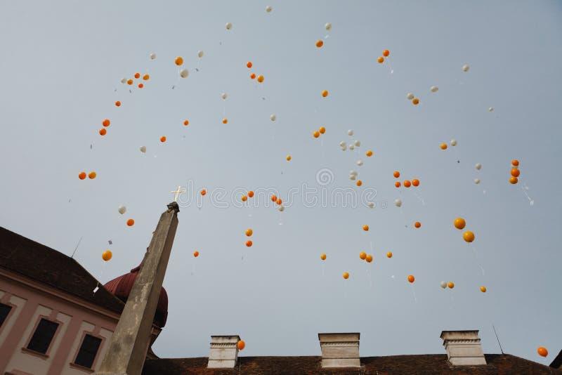 Liberação do balão do balão branco e alaranjado ao lado da igreja - cartões do desejo fotos de stock royalty free