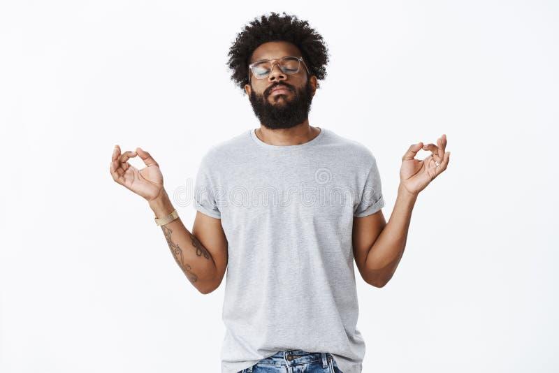 Liberando a press?o com medita??o Retrato do homem farpado afro-americano adulto calmo e calmo com tatuagens e imagem de stock royalty free