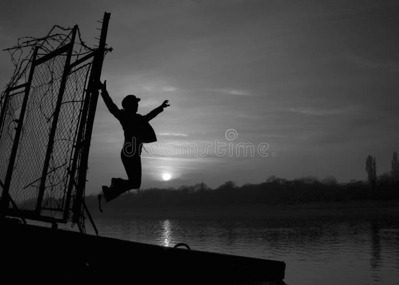 Liberation. Woman silhouette jumps away from the babed wire towards the Sun and open horizon royalty free stock photos