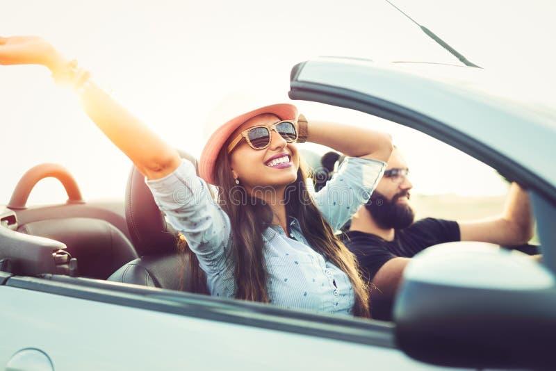 Liberdade da estrada aberta Pares novos que conduzem ao longo da estrada secundária no carro superior aberto foto de stock royalty free