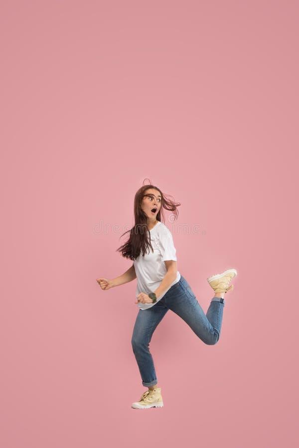Liberdade em mover-se Jovem mulher bonita que salta contra o fundo cor-de-rosa foto de stock royalty free