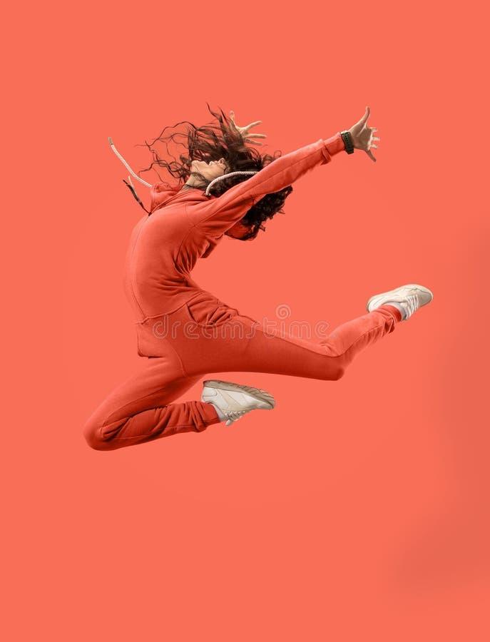 Liberdade em mover-se Jovem mulher bonita que salta contra o fundo coral imagem de stock