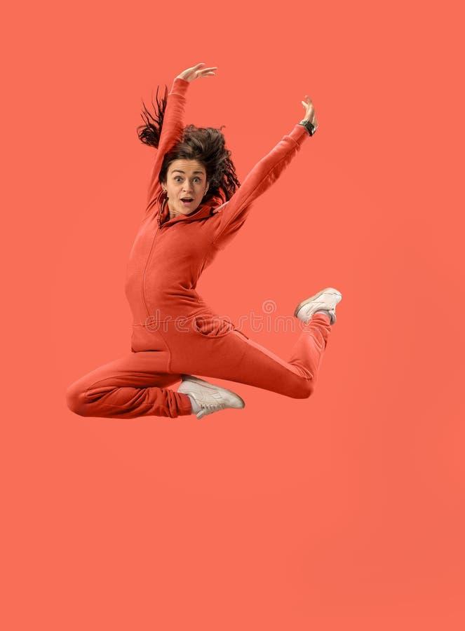 Liberdade em mover-se Jovem mulher bonita que salta contra o fundo coral imagens de stock royalty free