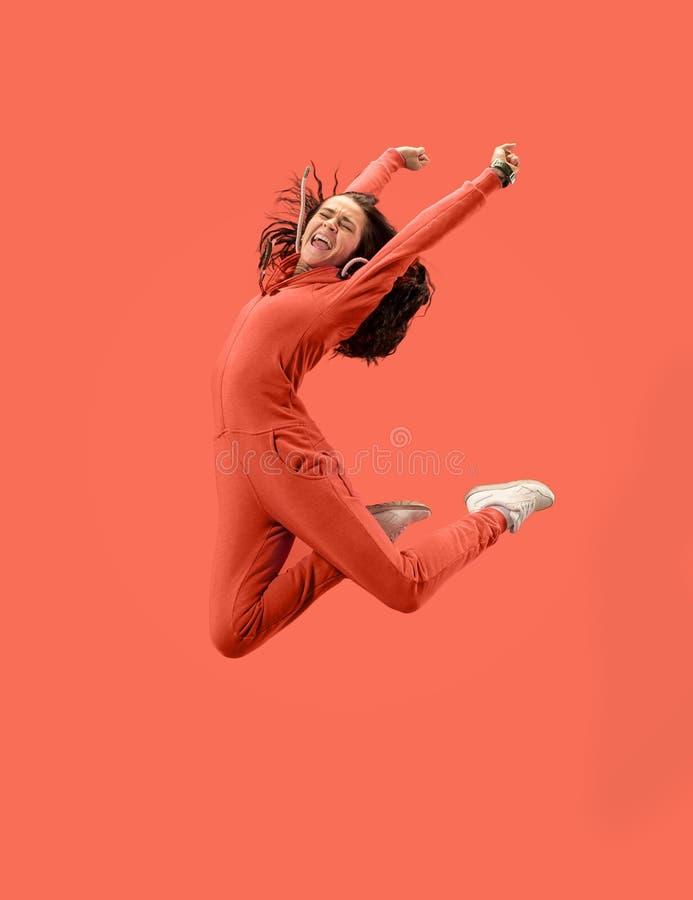 Liberdade em mover-se Jovem mulher bonita que salta contra o fundo coral foto de stock royalty free
