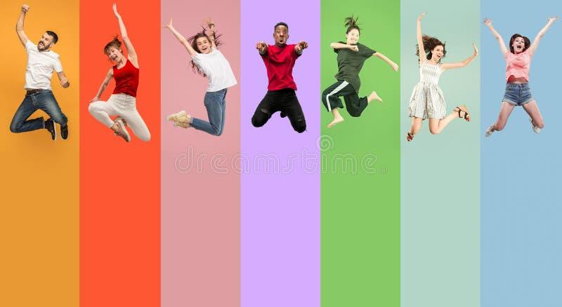 Liberdade em mover-se Jovens mulheres bonitas e homens que saltam contra o fundo colorido foto de stock