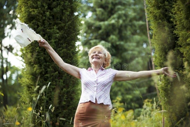 Liberdade. Senhora idosa feliz com cabana que sorri no jardim. Estilo de vida fotos de stock royalty free