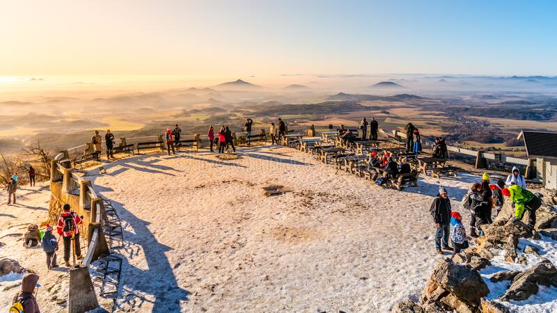 LIBEREC, CZECH REPUBLIC - JANUARY 2, 2020: Lookout terrace at Jested Mountain Hotel. Sunny winter day view of tourists. And foggy landscape. Liberec, Czech stock photography