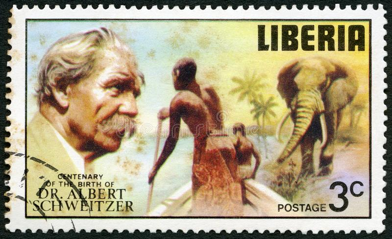 LIBERIA - 1975: shows elephant and tribesmen poling boat, serieselephant and tribesmen poling boat, series Dr. Albert Schweitzer stock photography
