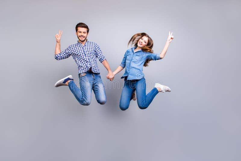 Libertà e divertimento, emozioni e sensibilità Le coppie allegre ed allegre in attrezzature casuali sono saltanti e gesturing i s immagini stock