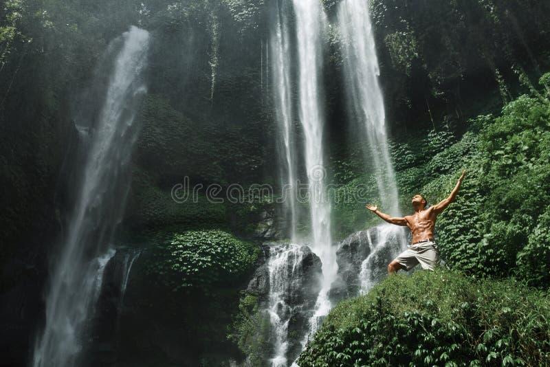 Libertà L'uomo che si sente libero con le mani aumenta vicino alla cascata immagini stock