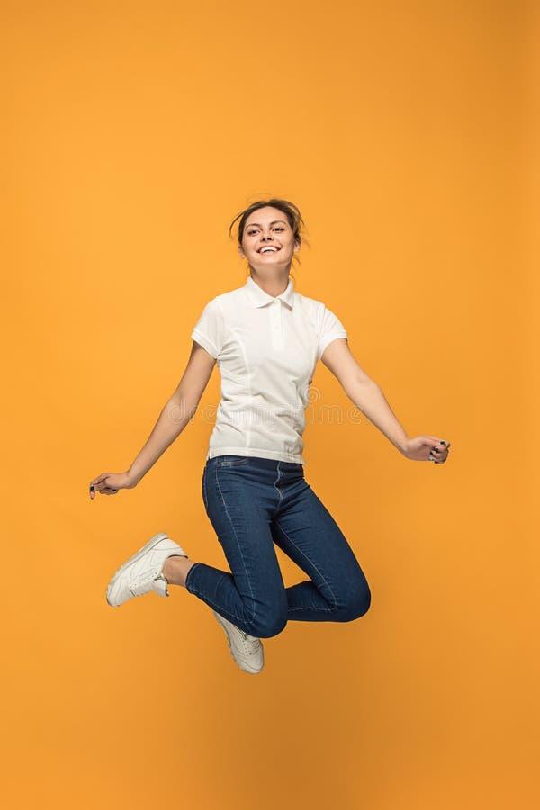 Libertà nel muoversi Giovane donna graziosa che salta contro il fondo arancio immagini stock