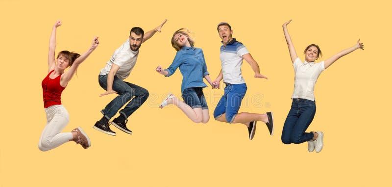 Liberté dans le déplacement jeune homme et femmes sautant sur le fond jaune photo libre de droits
