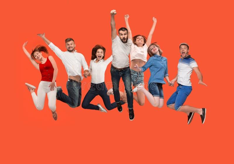 Liberté dans le déplacement jeune homme et femmes sautant sur le fond rouge photo libre de droits