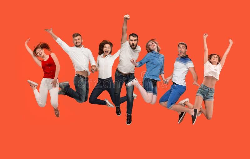 Liberté dans le déplacement jeune homme et femmes sautant sur le fond rouge image libre de droits