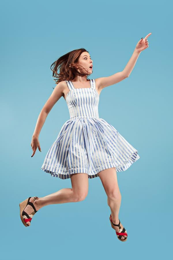 Liberté dans le déplacement Jolie jeune femme sautant sur le fond bleu photographie stock libre de droits