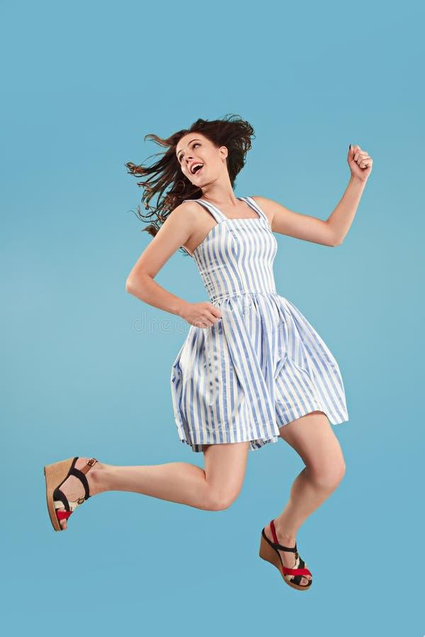 Liberté dans le déplacement Jolie jeune femme sautant sur le fond bleu photo stock