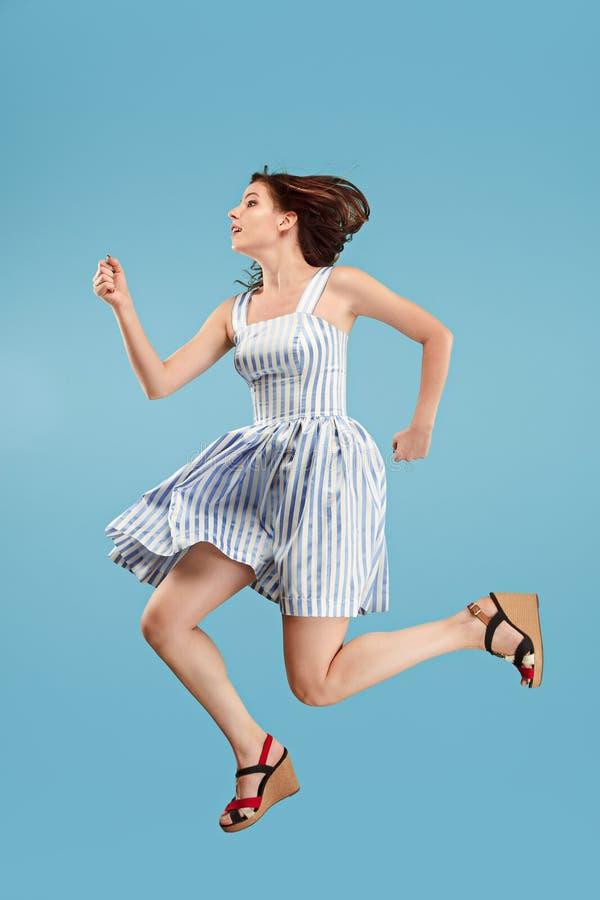 Liberté dans le déplacement Jolie jeune femme sautant sur le fond bleu image libre de droits