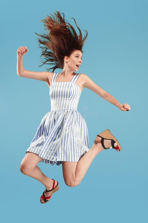 Liberté dans le déplacement Jolie jeune femme sautant sur le fond bleu photos libres de droits