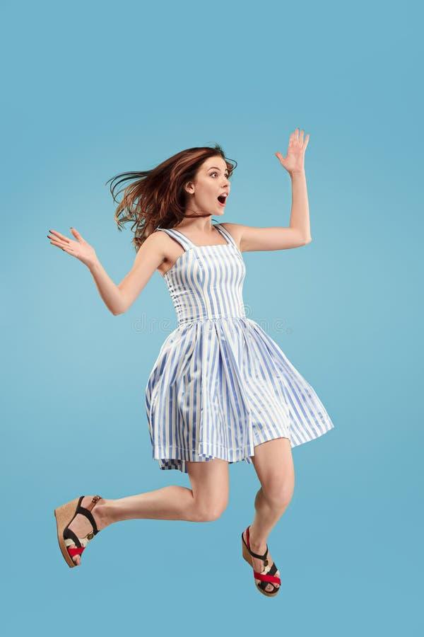 Liberté dans le déplacement Jolie jeune femme sautant sur le fond bleu images libres de droits